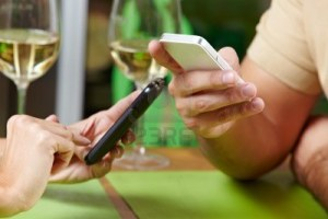 14333735-couple-using-their-smartphones-at-the-same-time-in-a-restaurant