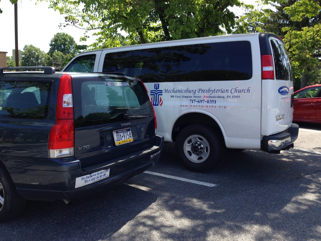 My car with its UCC bumper sticker, parked next to the Presbyterian van.
